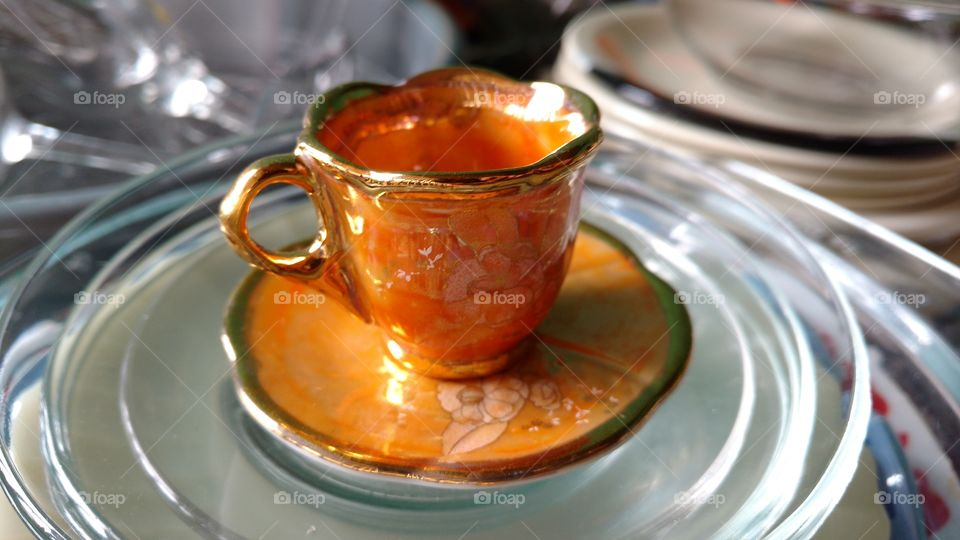 Gold colored cup on saucer