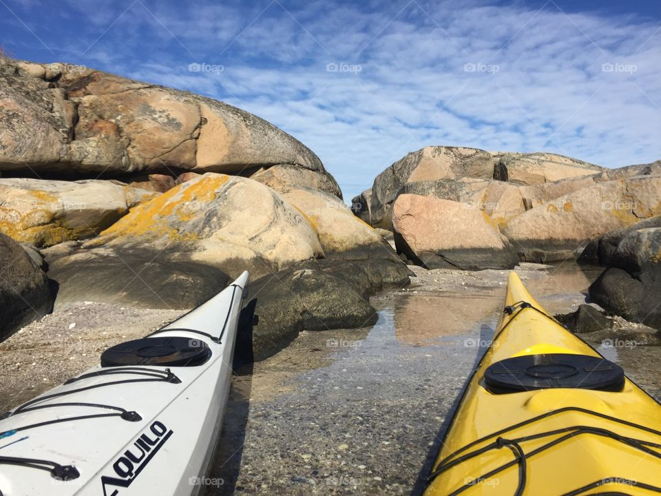 Rocks and two kayaks . Kayaks on the beach. Blue sky with white clouds.