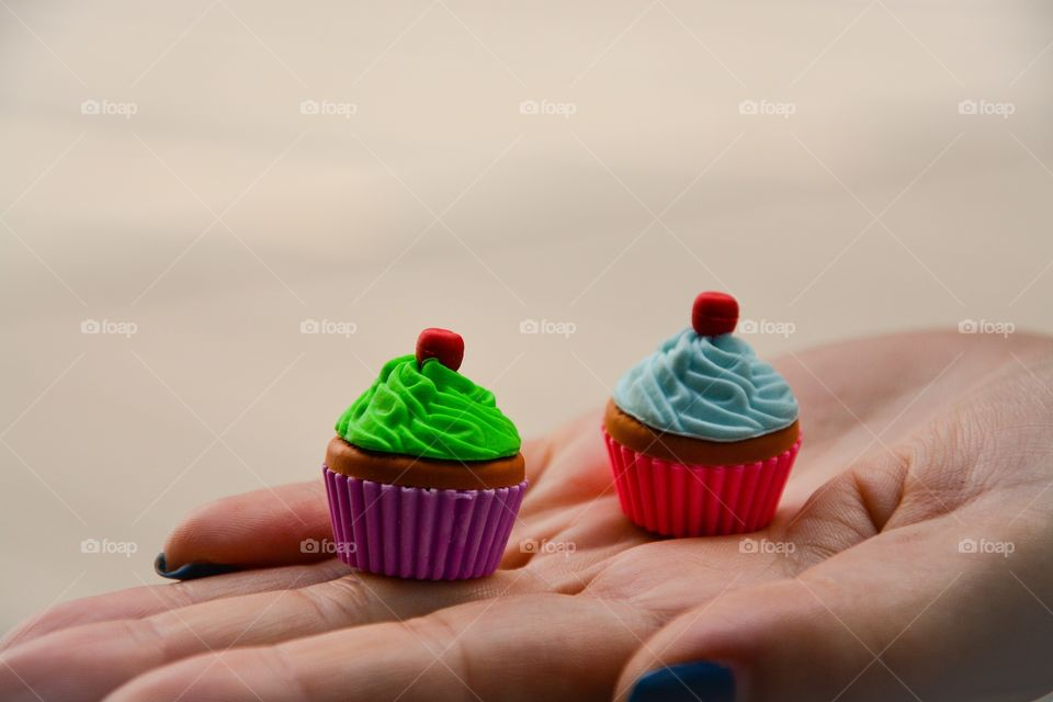 Hand of woman holding small muffins