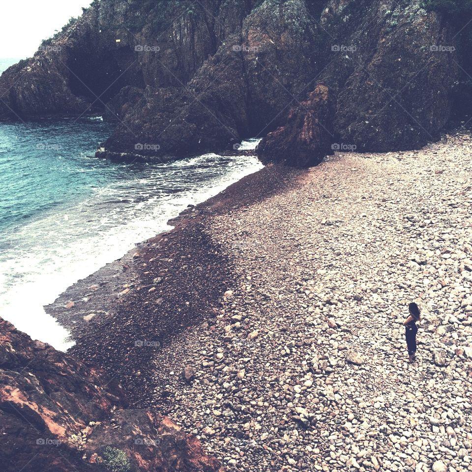 Girl alone on rocky Mediterranean beach. Girl alone on rocky Mediterranean beach with blue water and cliffs surrounding.