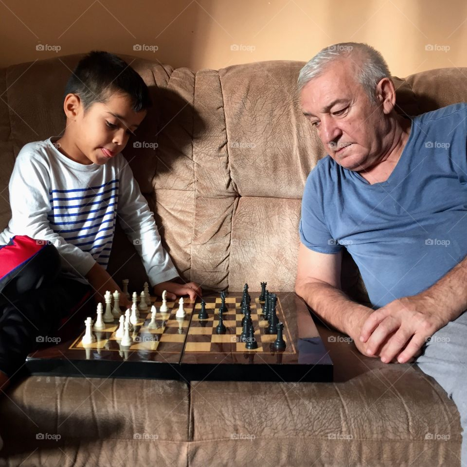 Young boy is playing chess with his grandfather at home