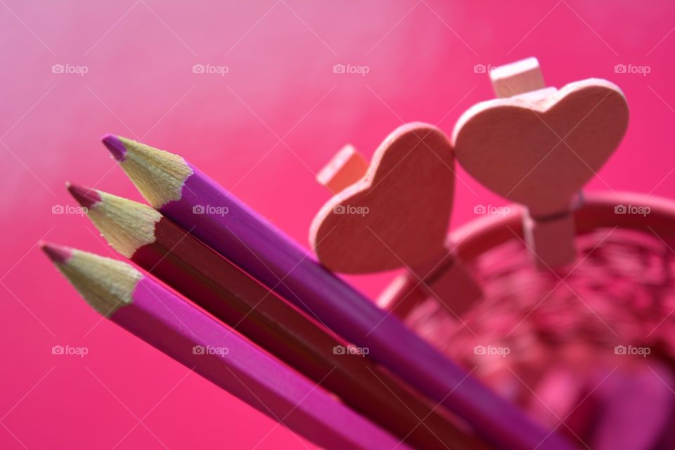 pink color wooden pen and wood hearts  pink background