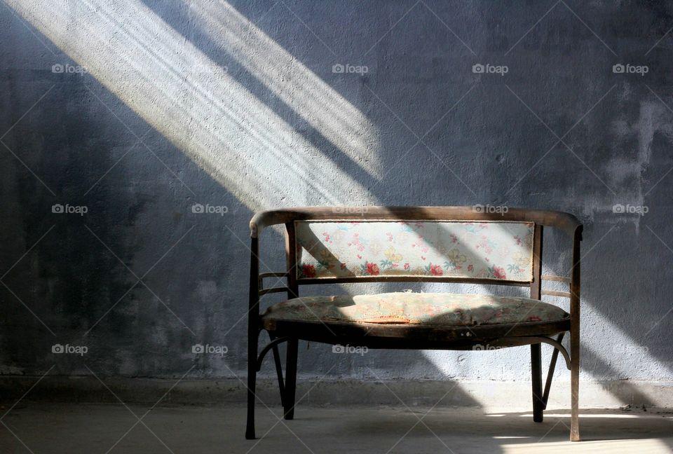 Empty bench indoor, sunlight beams over it