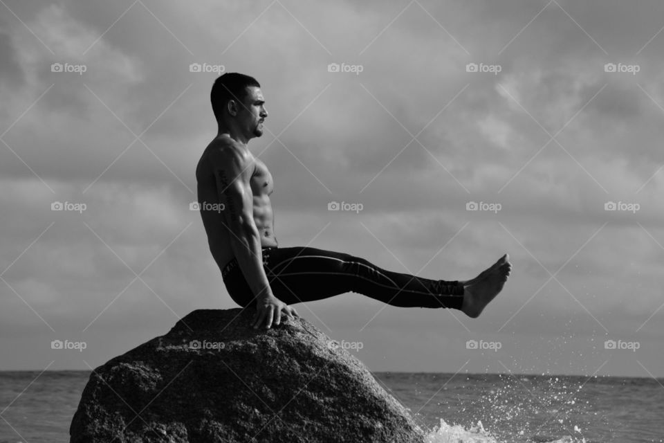 Muscular shirtless man exercise on rock in sea