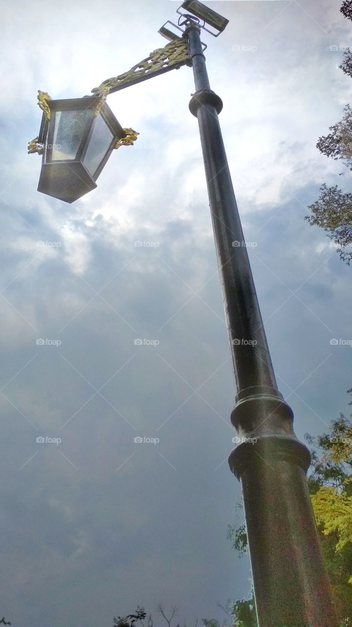 Standing beneath a lamp looking at the sky after rain, then comes the sun, giving its shine.