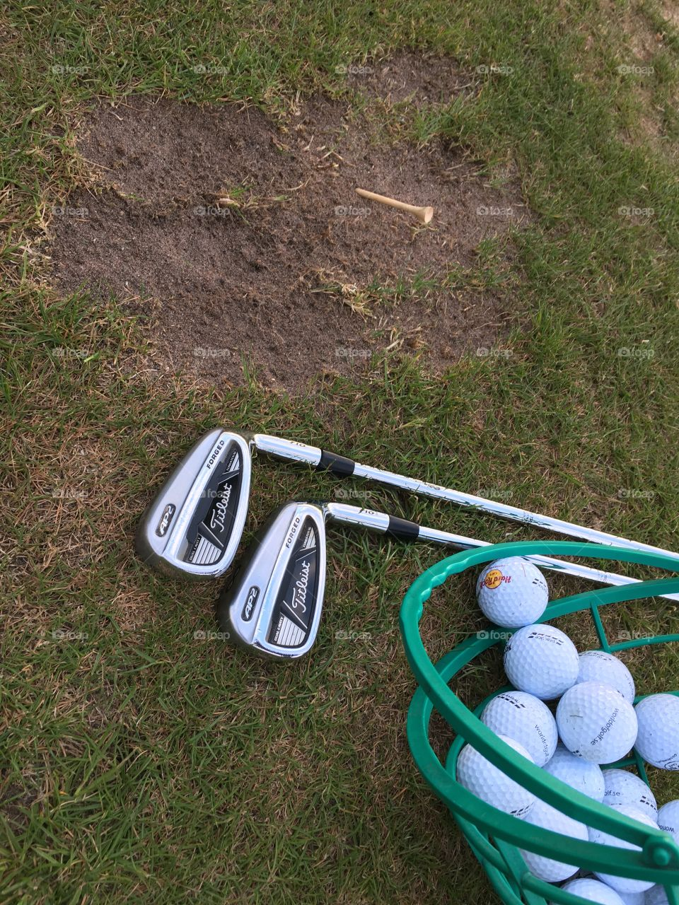 Titleist iron golf clubs and a bucket of driving range balls on the grass surface