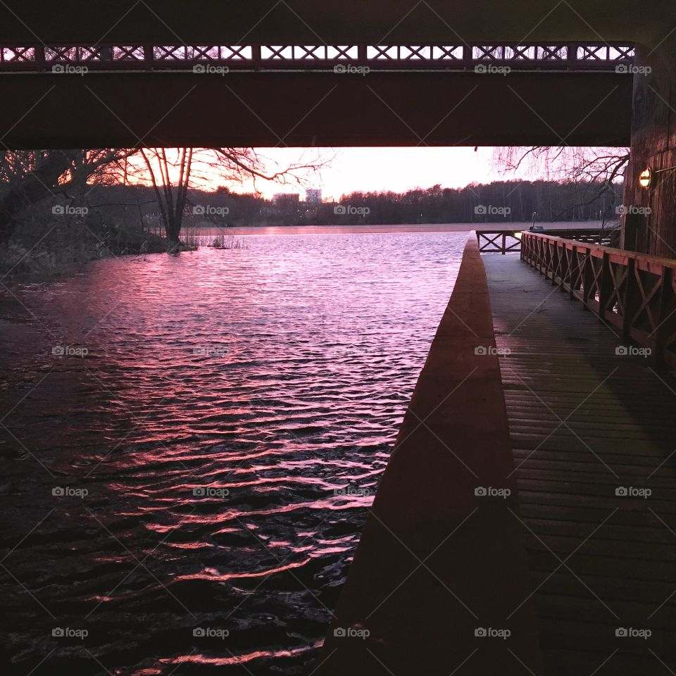 Small walking bridge along purple reflections at waterline