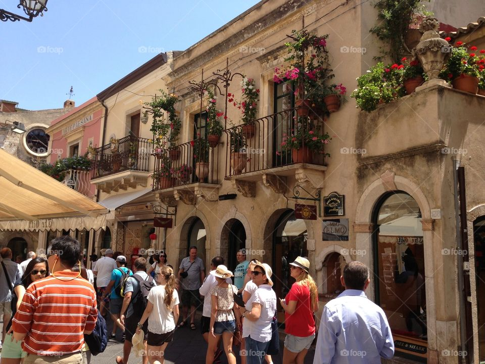 People in holiday. People is walking in the village between the houses in Taormina,Italy