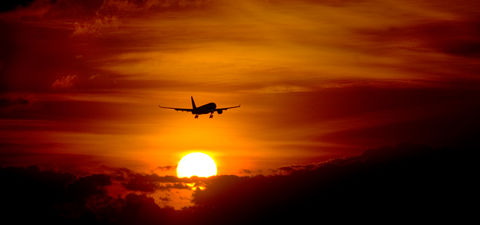 Silhouette of airplane in sky during sunset