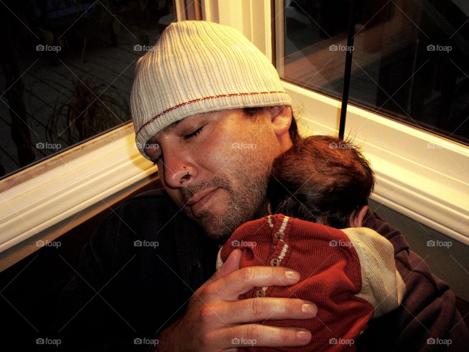 Newborn baby sleeping on father's shoulder