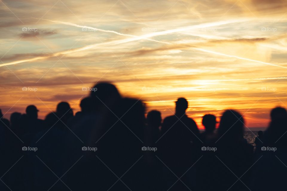 People standing on beach during sunset with giant 'X' in the sky written with clouds. . Silhouette of crowd standing watching sunset