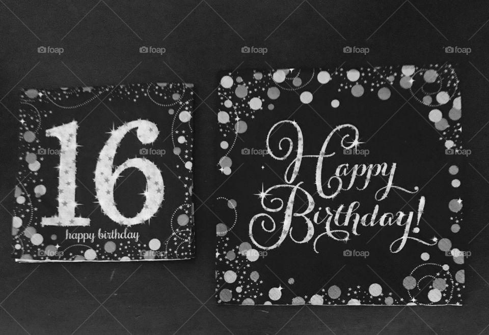 A display of happy birthday napkins black-and-white photo, sweet 16 birthday party. USA, America