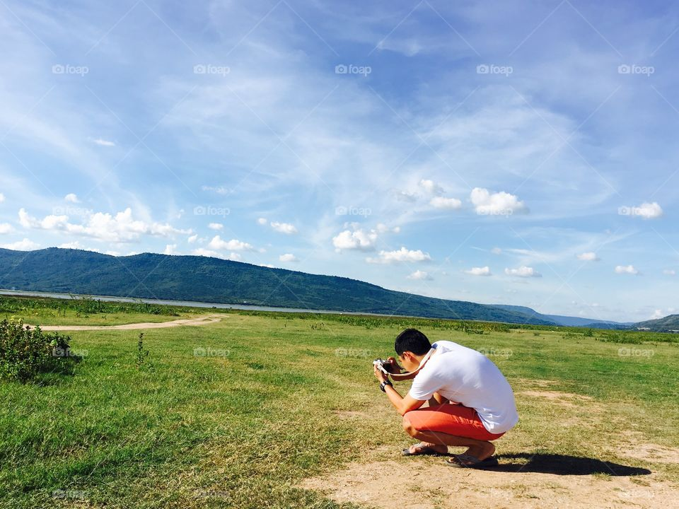 man take a photo in natural with mountain and green grass and lake,man take a photo among grass landscape and blue sky