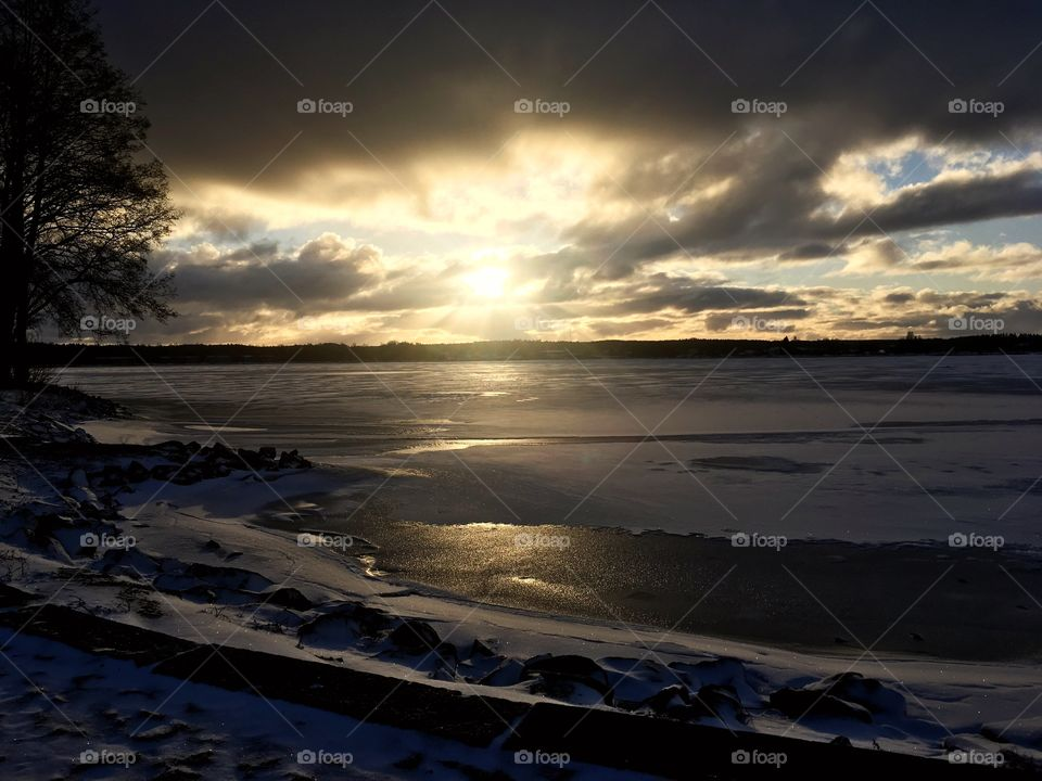 Sunsetting creates beautiful shadows and colors all around to the coastline. Cold winter weather and icy lake.