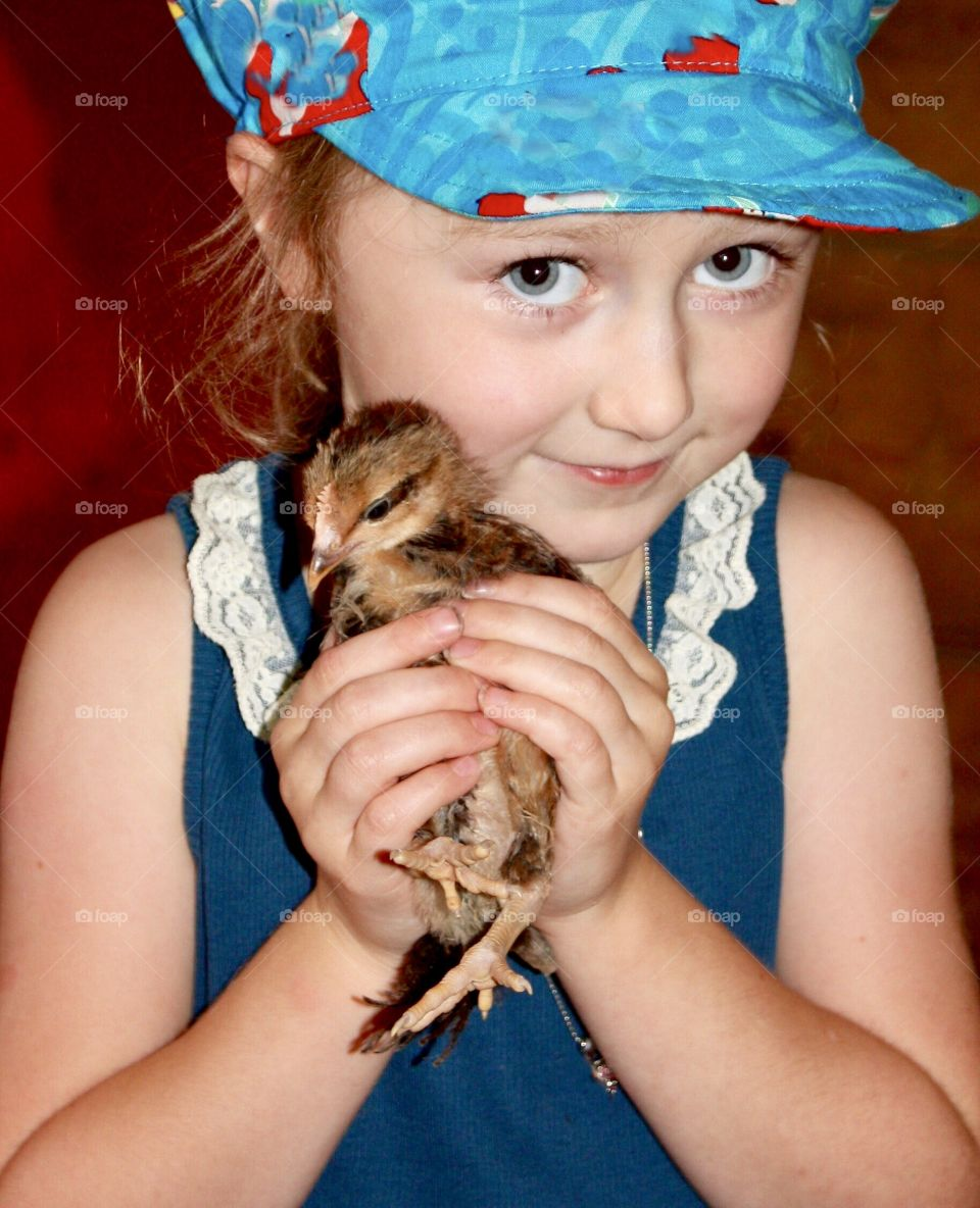 Girl tenderly holding a fuzzy chick - adorable