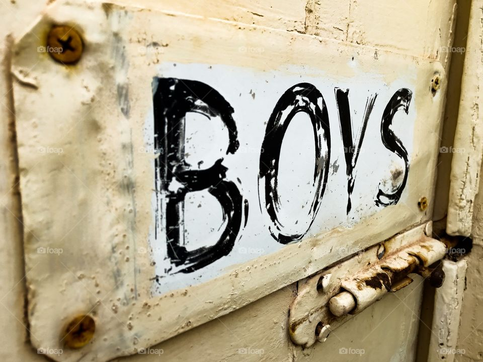 Old rusted painted tin sign on old door marked BOYS. Outdoor loo, outdoor John, outdoor toilet