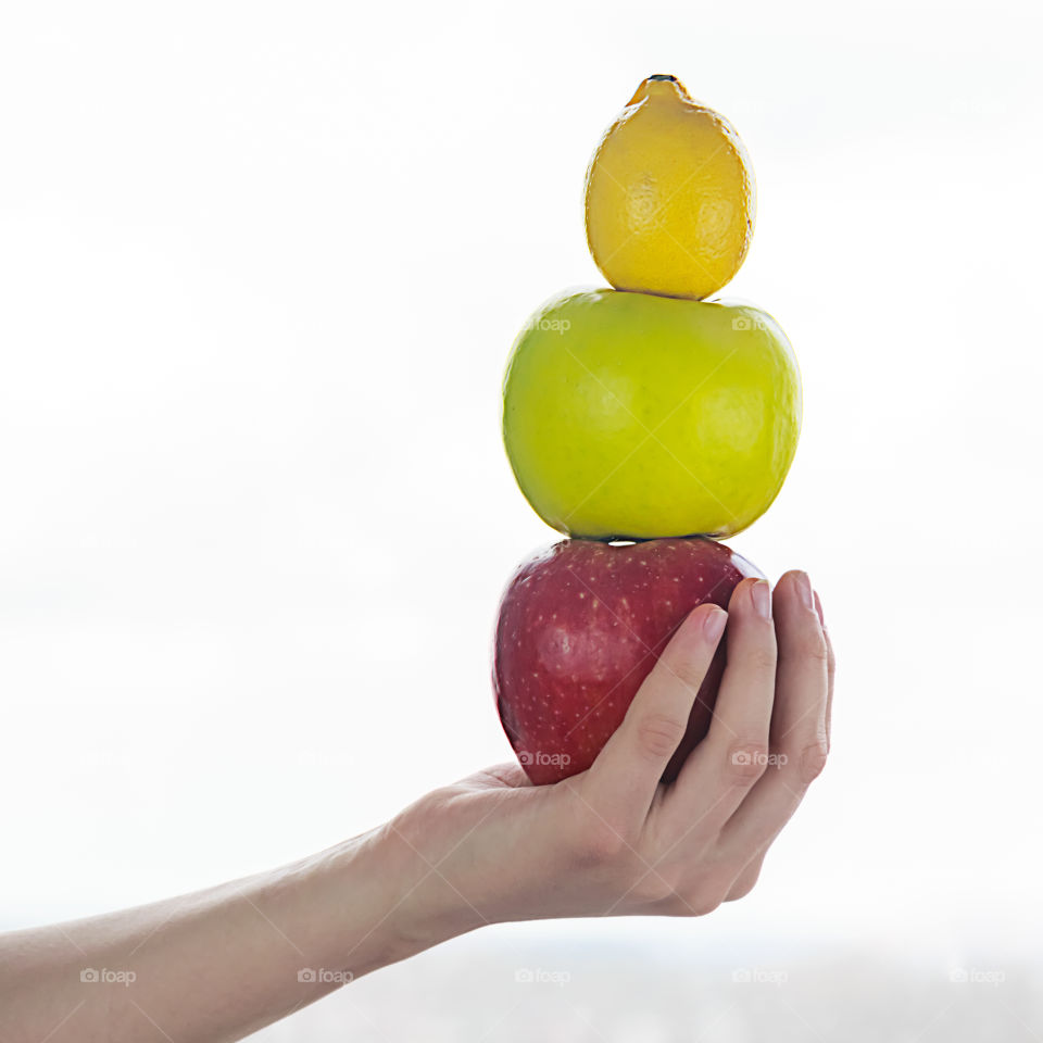 Woman holding stack of fruits