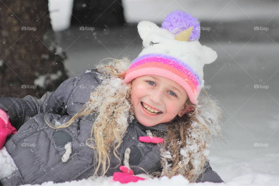 This sweet little girl is all smiles rolling around in the freshly fallen snow in her fuzzy unicorn hat.