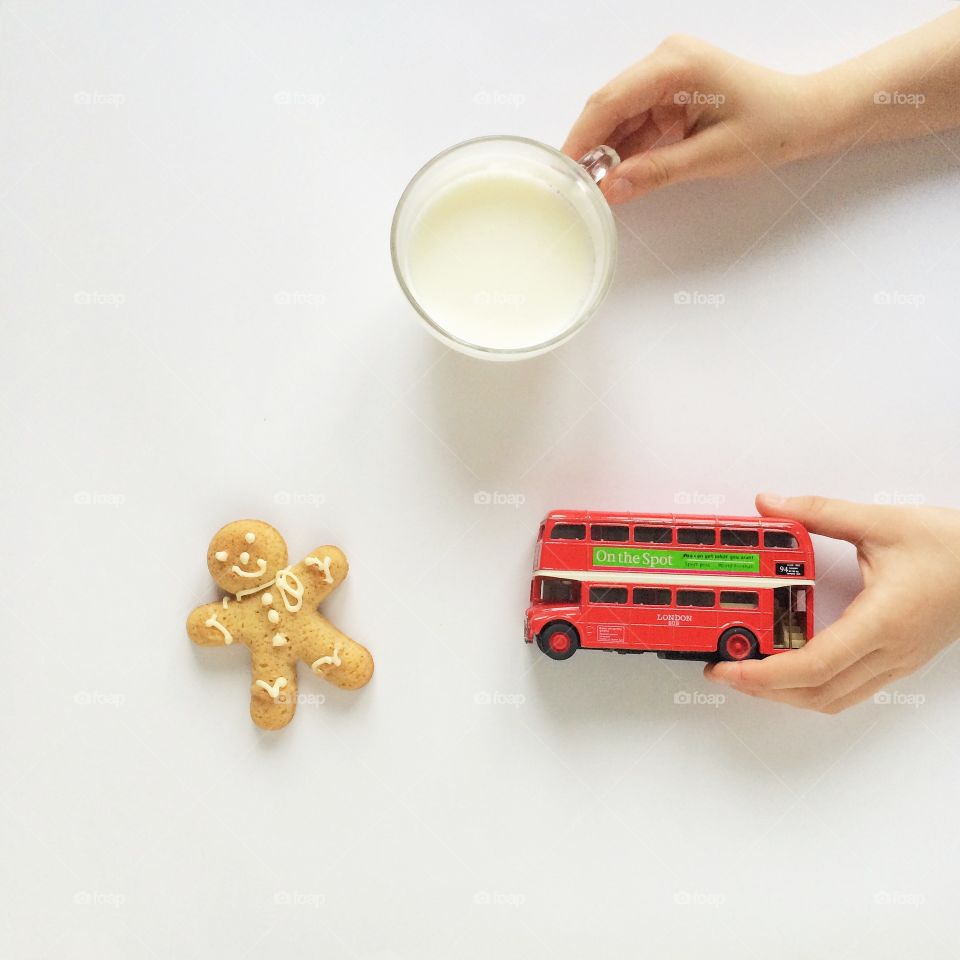 Person holding cup of milk and toy bus