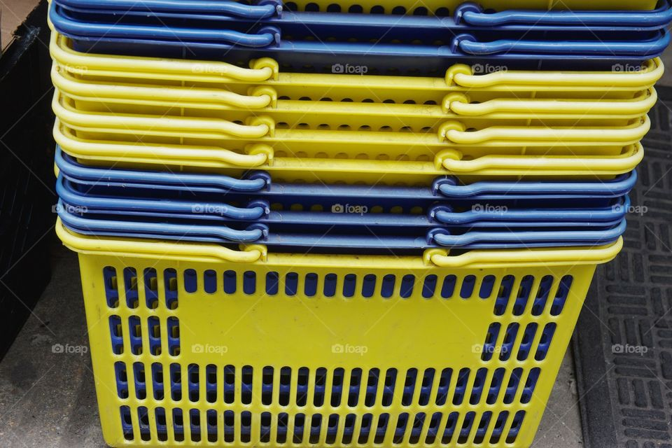 Yellow and blue stacked yellow shopping baskets outside a general merchandise retailer in Brooklyn, New York City.