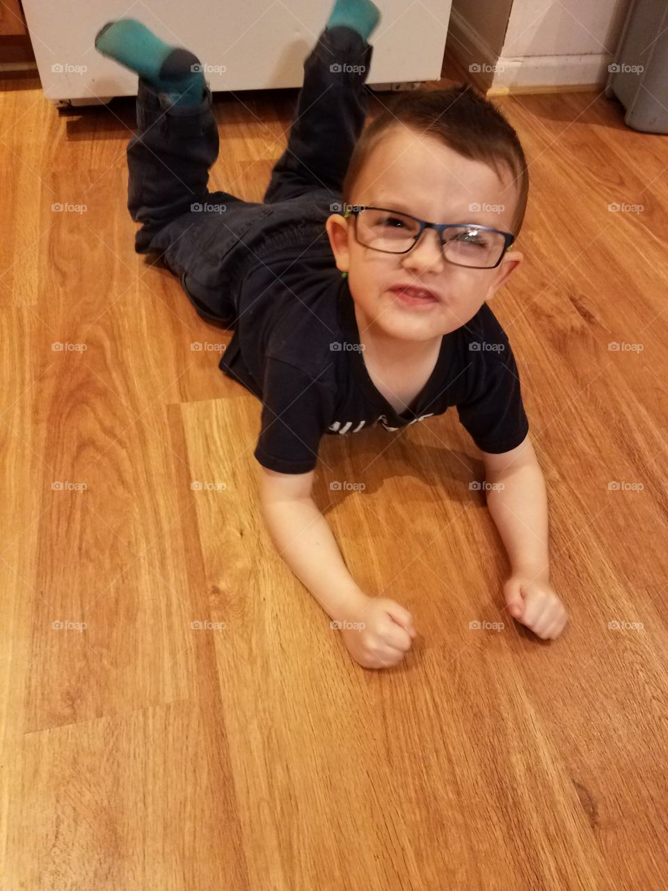 Little boy lying on floor with spectacles