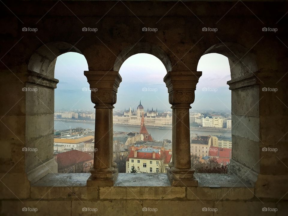 The Hungarian Parliament between pillars of a castle across the river separating Buda from Pest