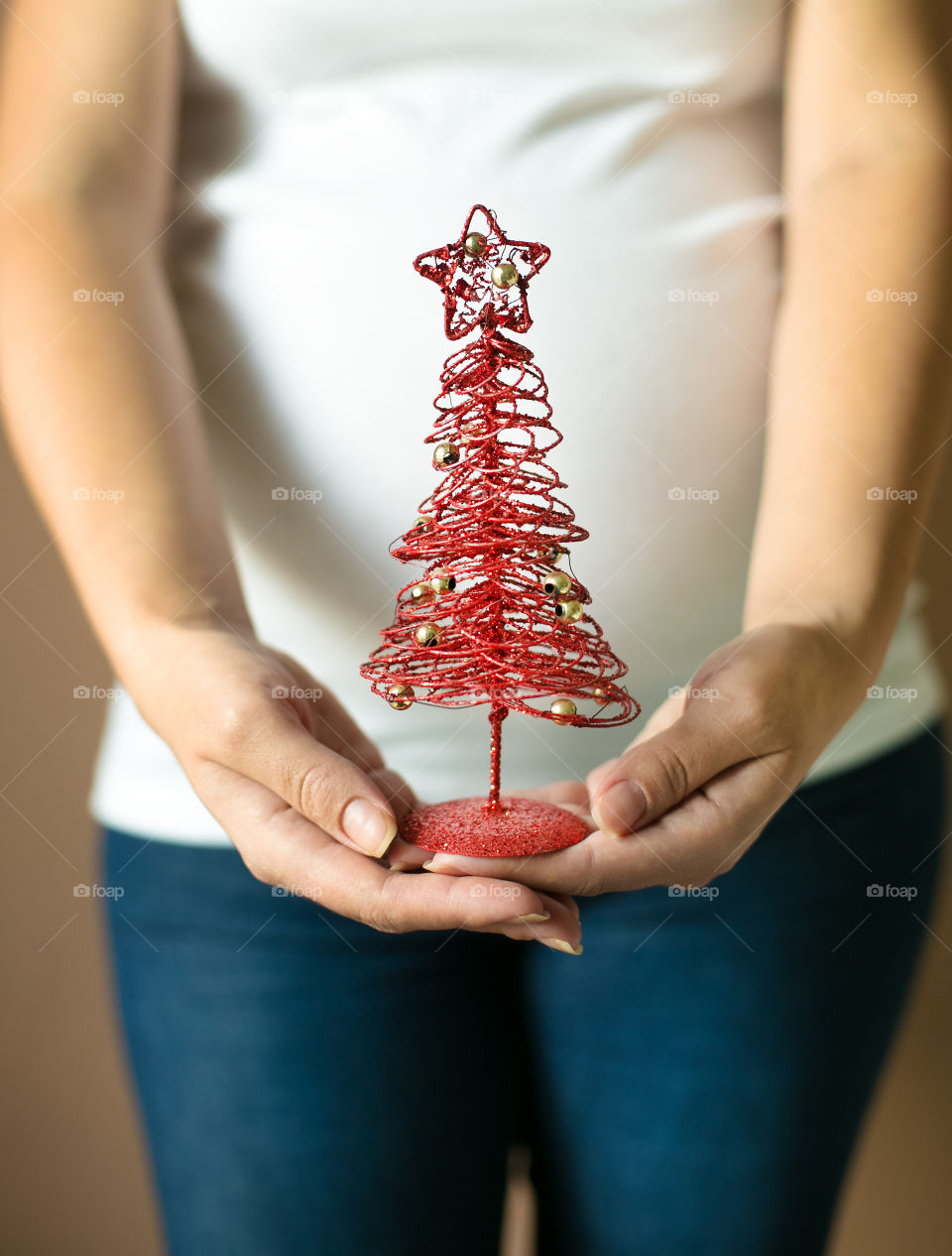 Midsection view of pregnant woman holding Christmas tree
