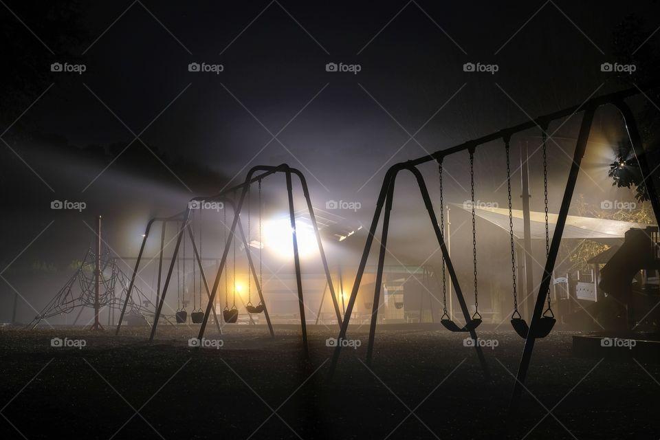 Swing sets backlit by streetlights on a dark foggy morning. Lake Benson Park in Garner North Carolina.