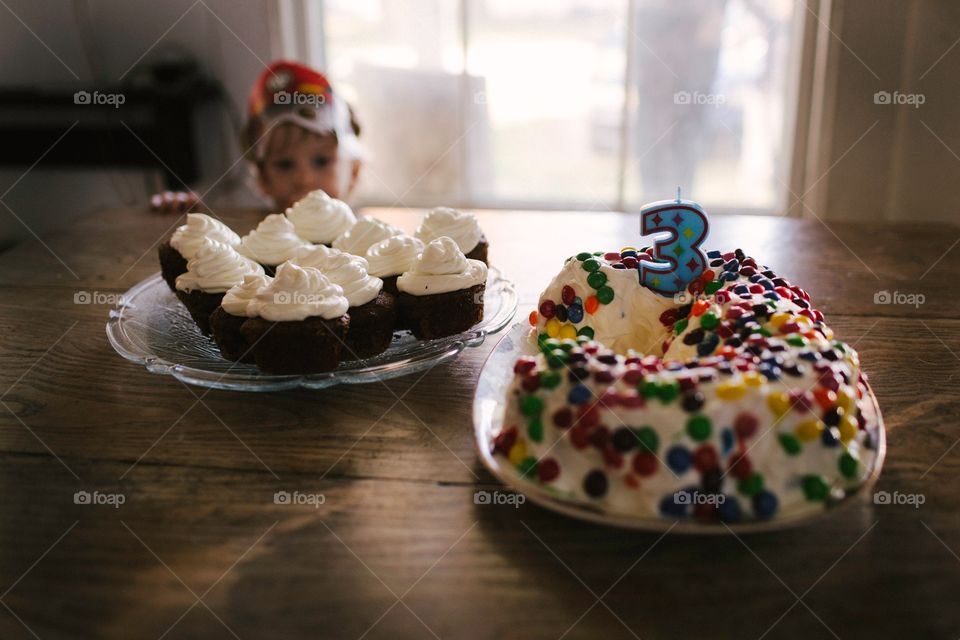 Three year old child looking longingly at a birthday cake. Staring over table at birthday cake and cupcakes