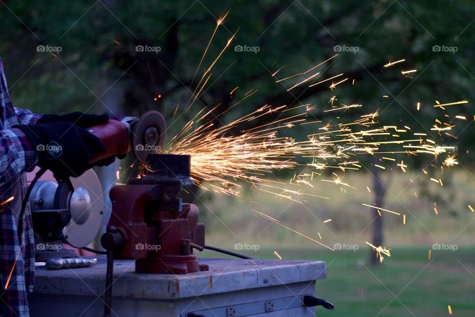 Side view of sparks from a bench grinder being used by a man on a metal part