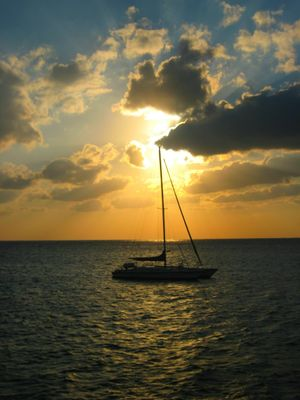 Silhouette of sailboat against dramatic sky