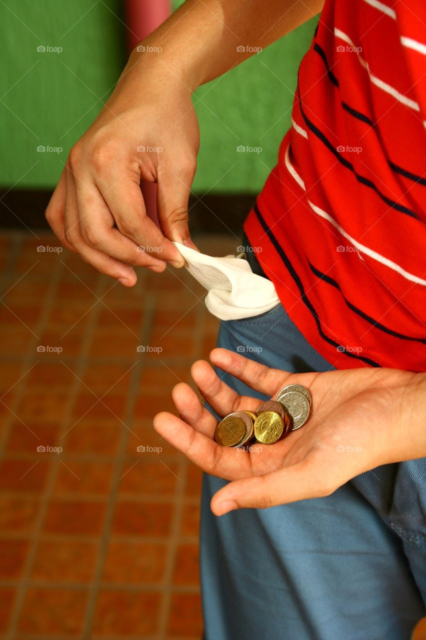 person holding coins in his hand and showing empty pocket