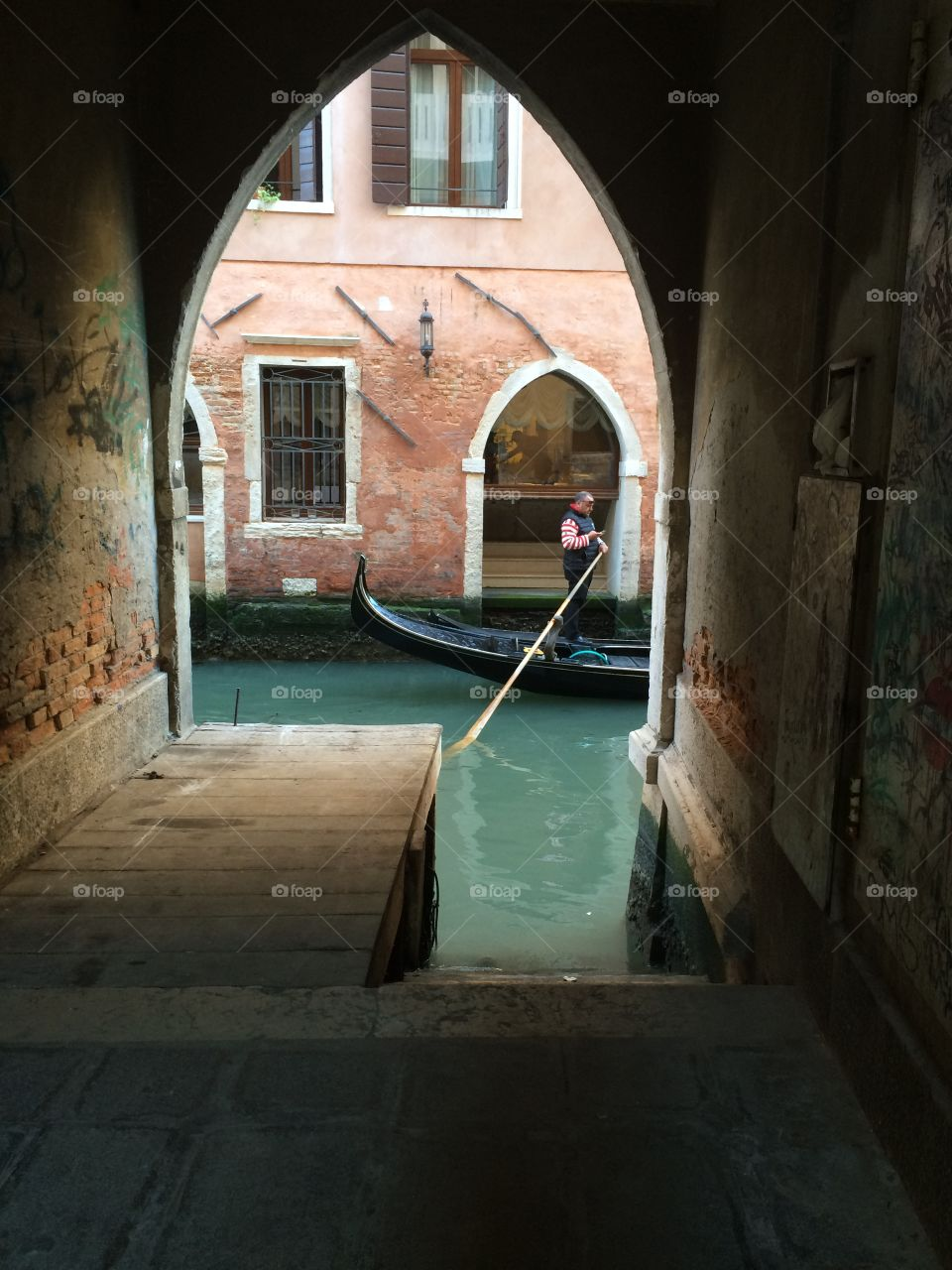 Dead end road in Venice with Gondola passing by on the canal.