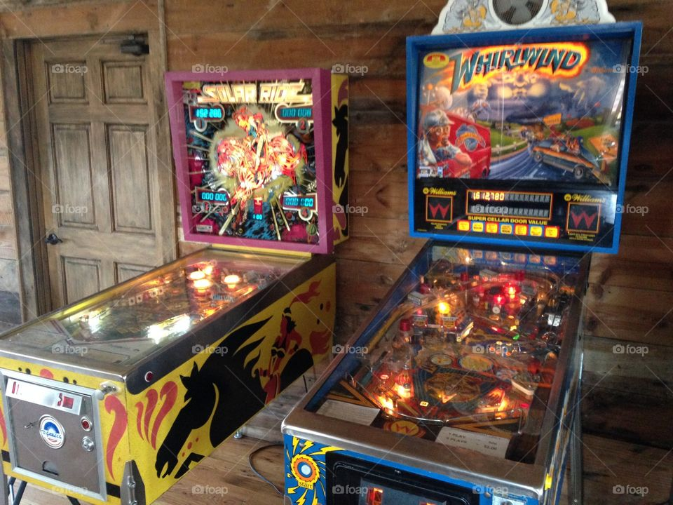 Pinball Machines. Two old school pinball games in front of wooded wall
