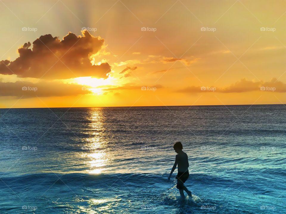 Beautiful golden sunset and azure seas surround a small joyful boy.