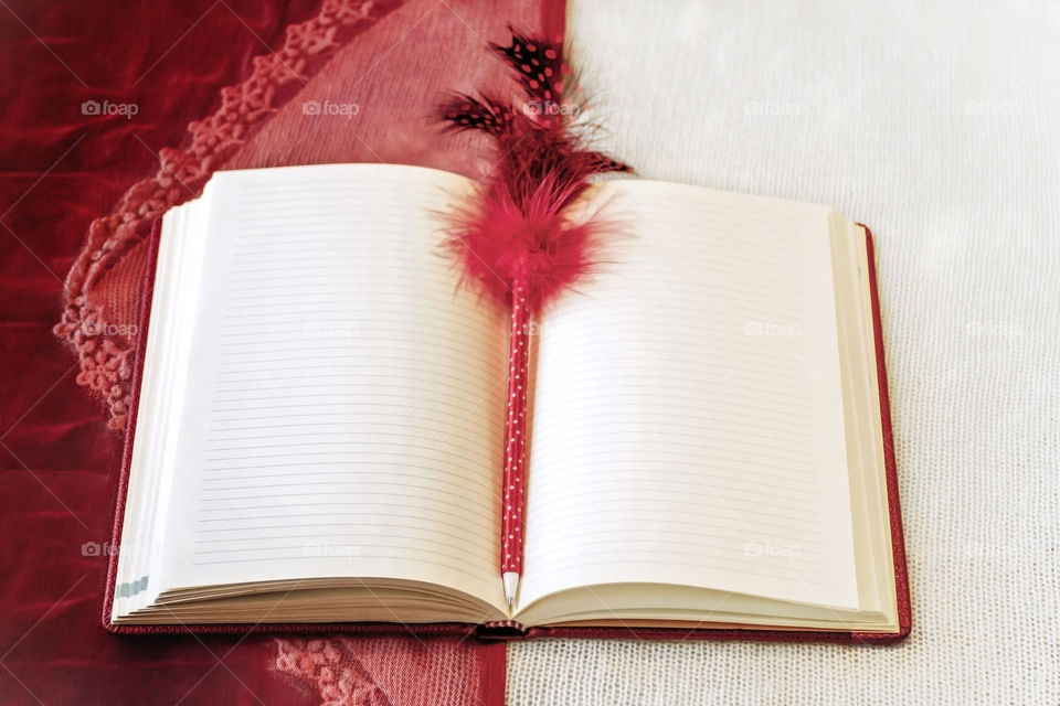 Notebook for writing in expanded form.In the center of the composition lies a pen decorated with a red feather.Red and white background in the background