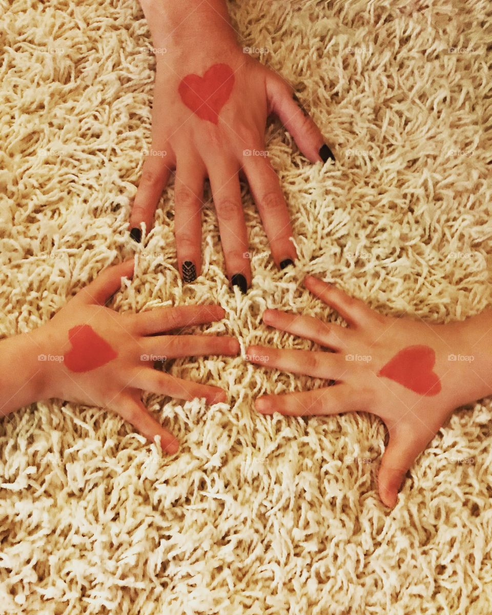 Mommy daughter and son's hands with a red heart