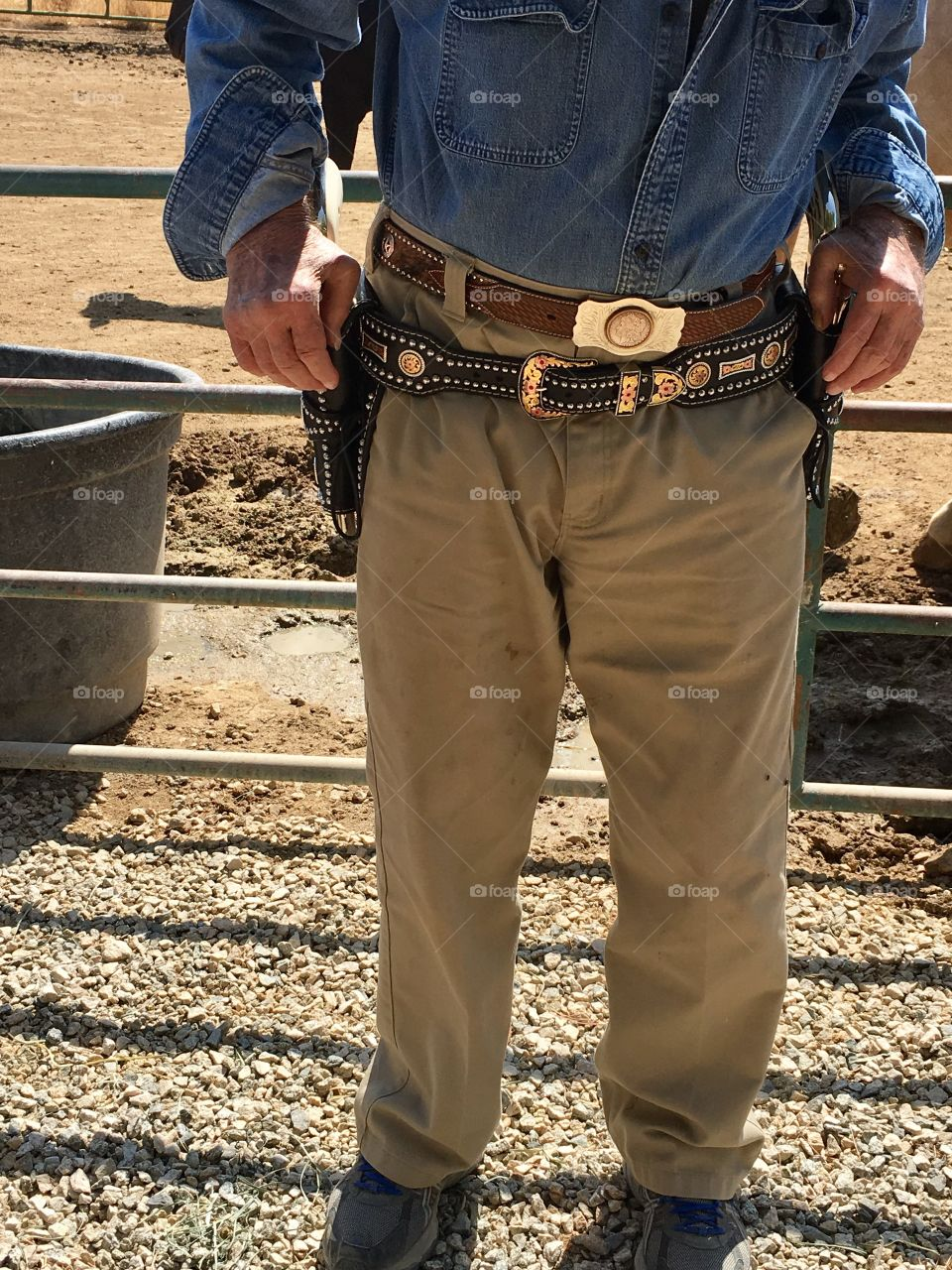Old senior cowboy wearing fun holsters and belt
