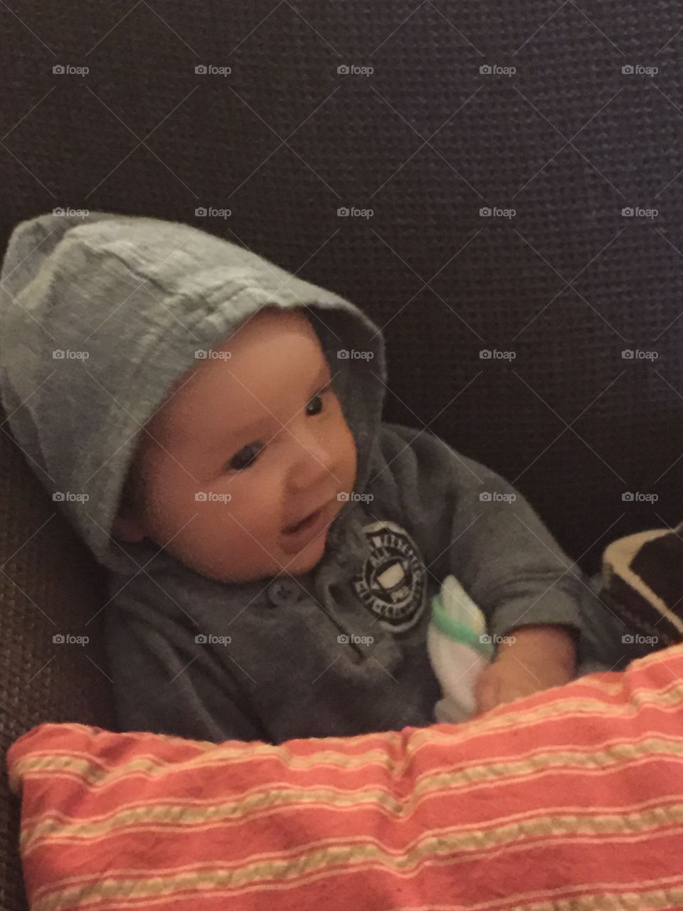 Two month old baby with a little hoodie on semi sitting on couch.