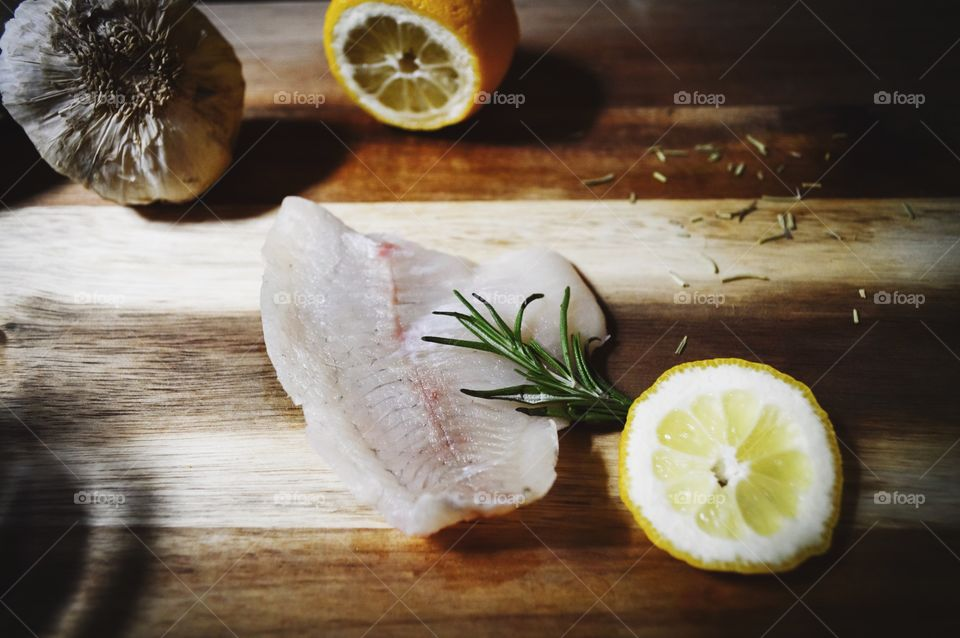 Raw fish fillet garnished with rosemary and lemon on wood surface