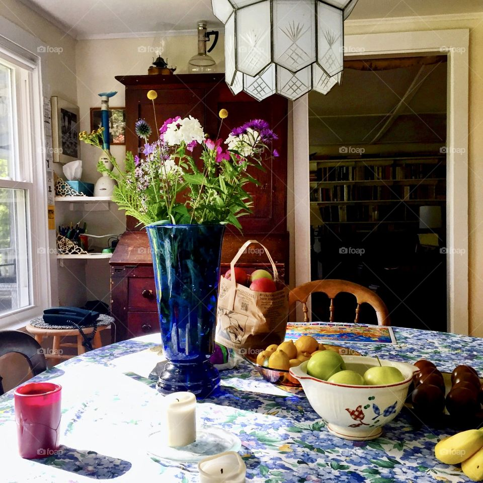 Sun drenched breakfast table with flowers and fruit