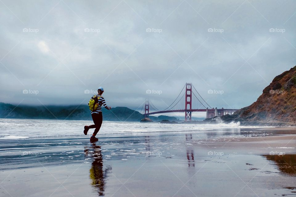 A lady runner running on Baker Beach in San Francisco towards the Golden Gate Bridge.