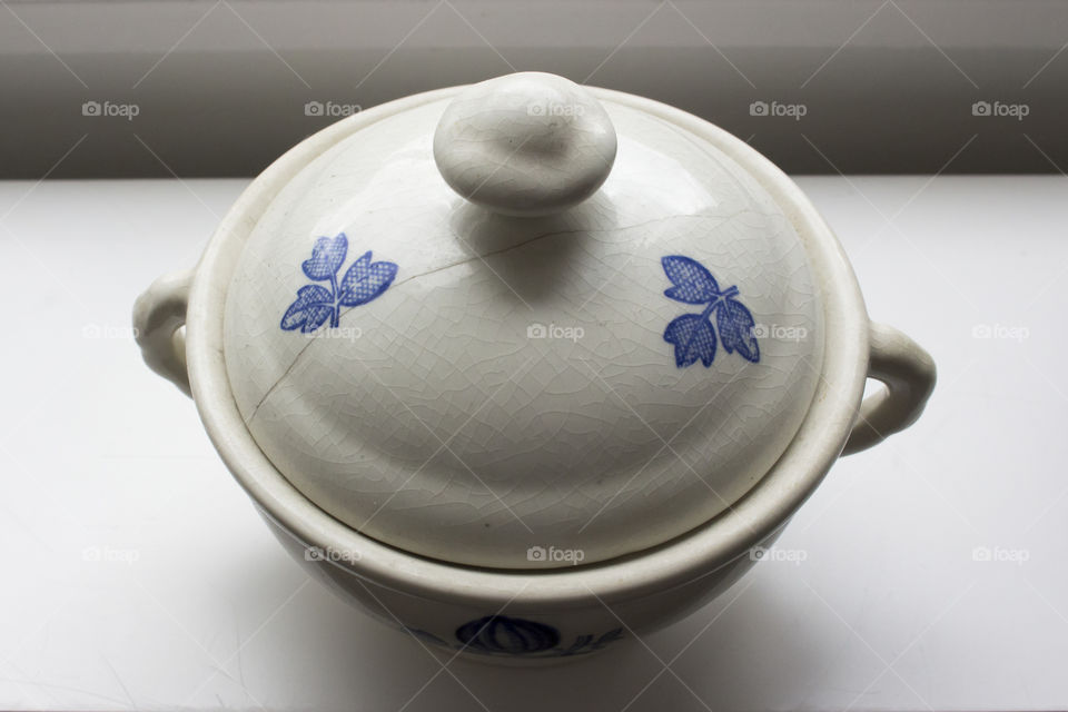 Old white and blue porcelain bowl with crackled lid