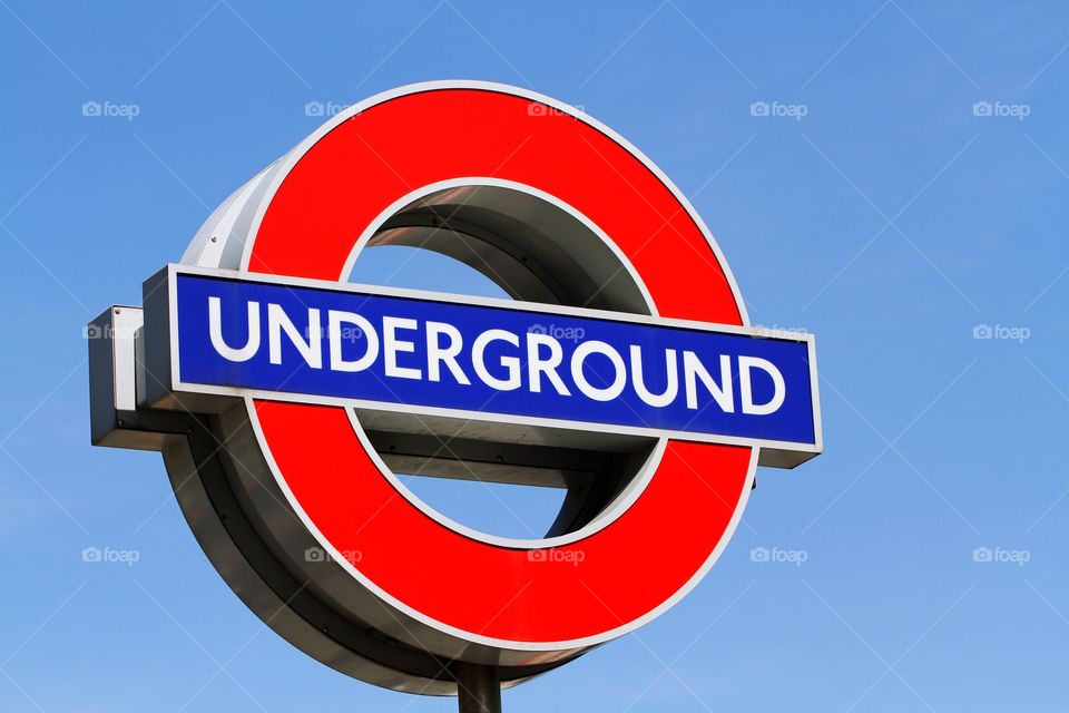 A colourful London Underground sign with a clear blue sky behind.