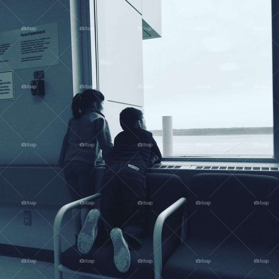Children waiting at the airport to pick up their Dad.