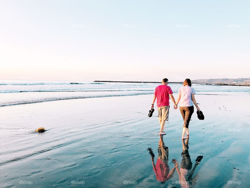 Happy loving couple walking barefoot on the beach at low tide, holding hands.