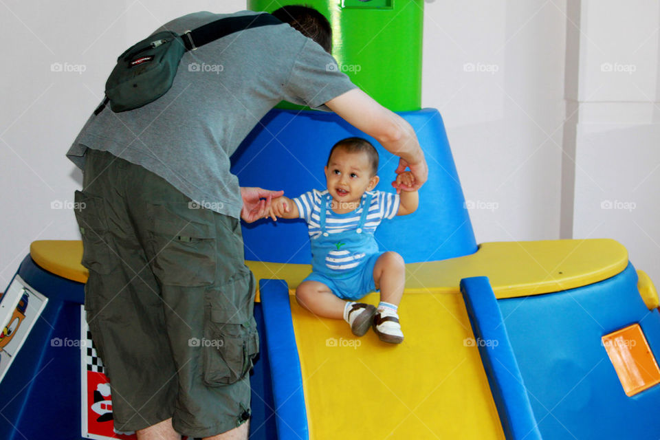 father helping  his son to slide