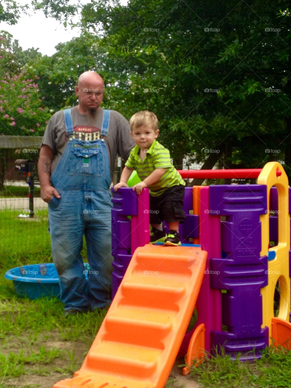 Pawpaw helping grandson playing on a plastic toys. Pawpaw wearing  denim overalls