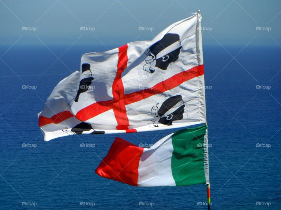 Sardinian and Italian flags in front of mediterranean sea
