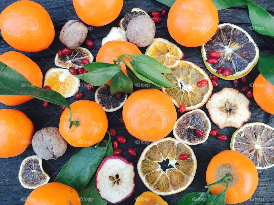 Tangerines with leaves and orange slices on wooden table